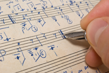 Hand with pen and music sheet - musical background